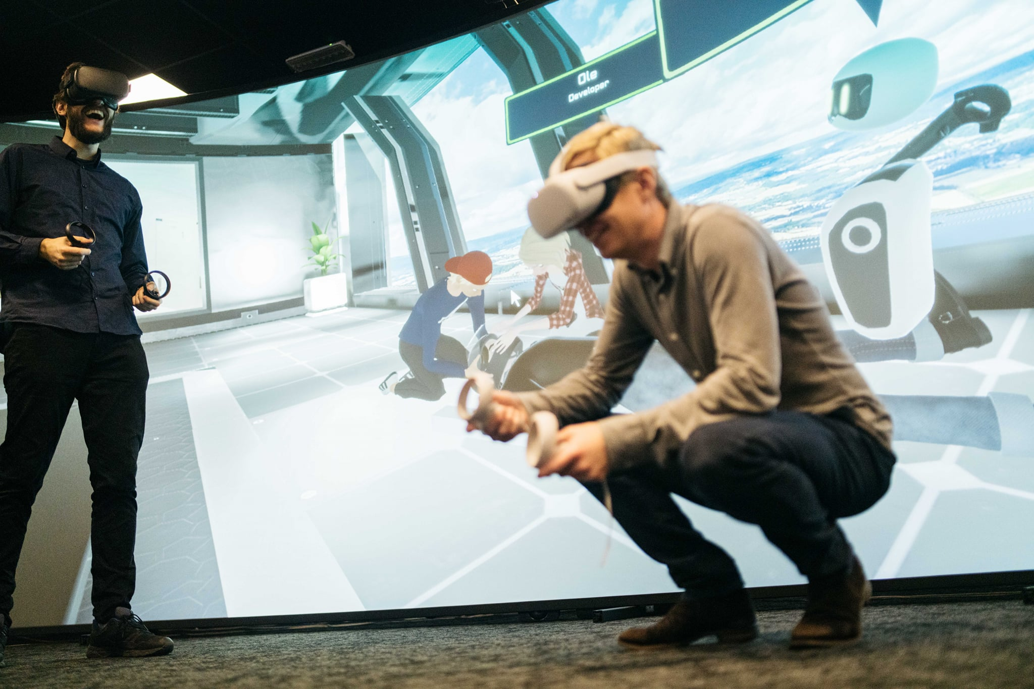 Fynd Reality employees wearing VR headsets; in the background there's a canvas showing a immersive learning scene in virtual reality.