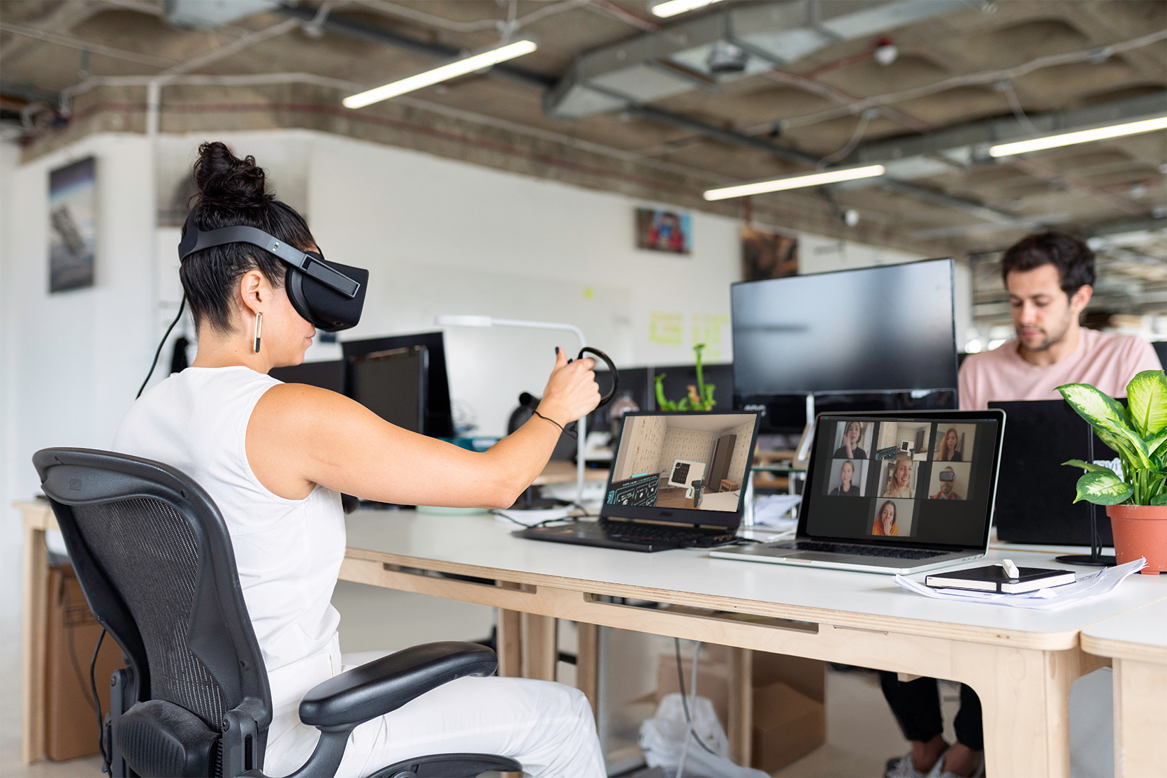 A woman in a clean office setting wearing a VR headset, using immersive learning in front of her laptop.