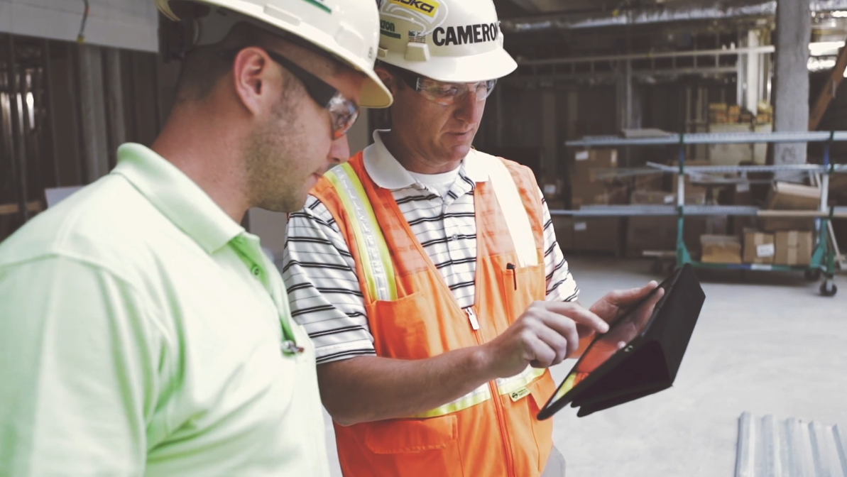 Two construction workers looking at a digital twin a tablet
